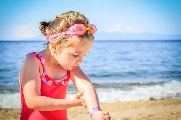 Dieťa na pláži sa opaľuje, cestovanie