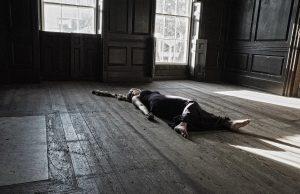 žena leží na podlahe domu
